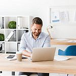 happy bearded man sitting in office working 4HVP863 150x150 1