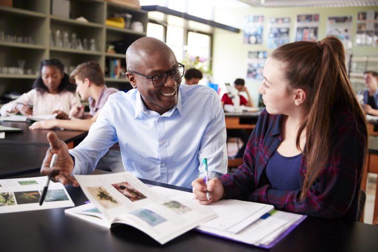 high school tutor sitting at desk with female BKHVWRX