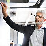mature businessman with gray hair in the office PJ8CDSM 150x150 1