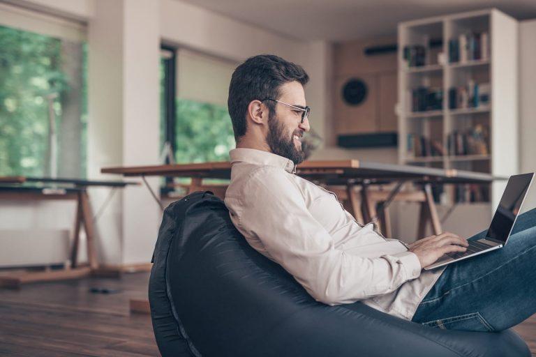 smiling man with laptop indoors B3U679G