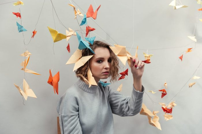 woman standing among colorful origami PZ9GKAU