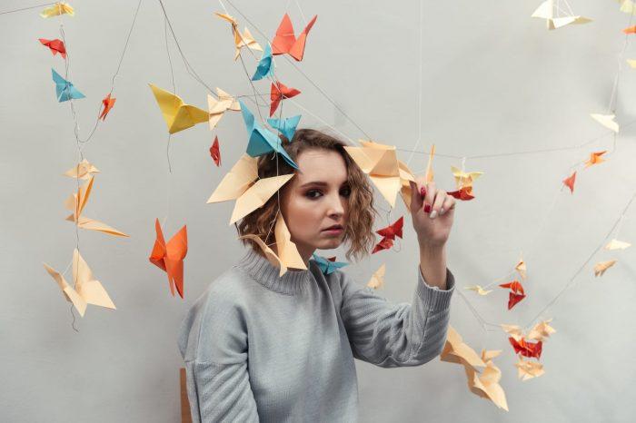 woman standing among colorful origami PZ9GKAU