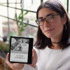 mockup of a woman with glasses holding a kindle oasis by a window 26068