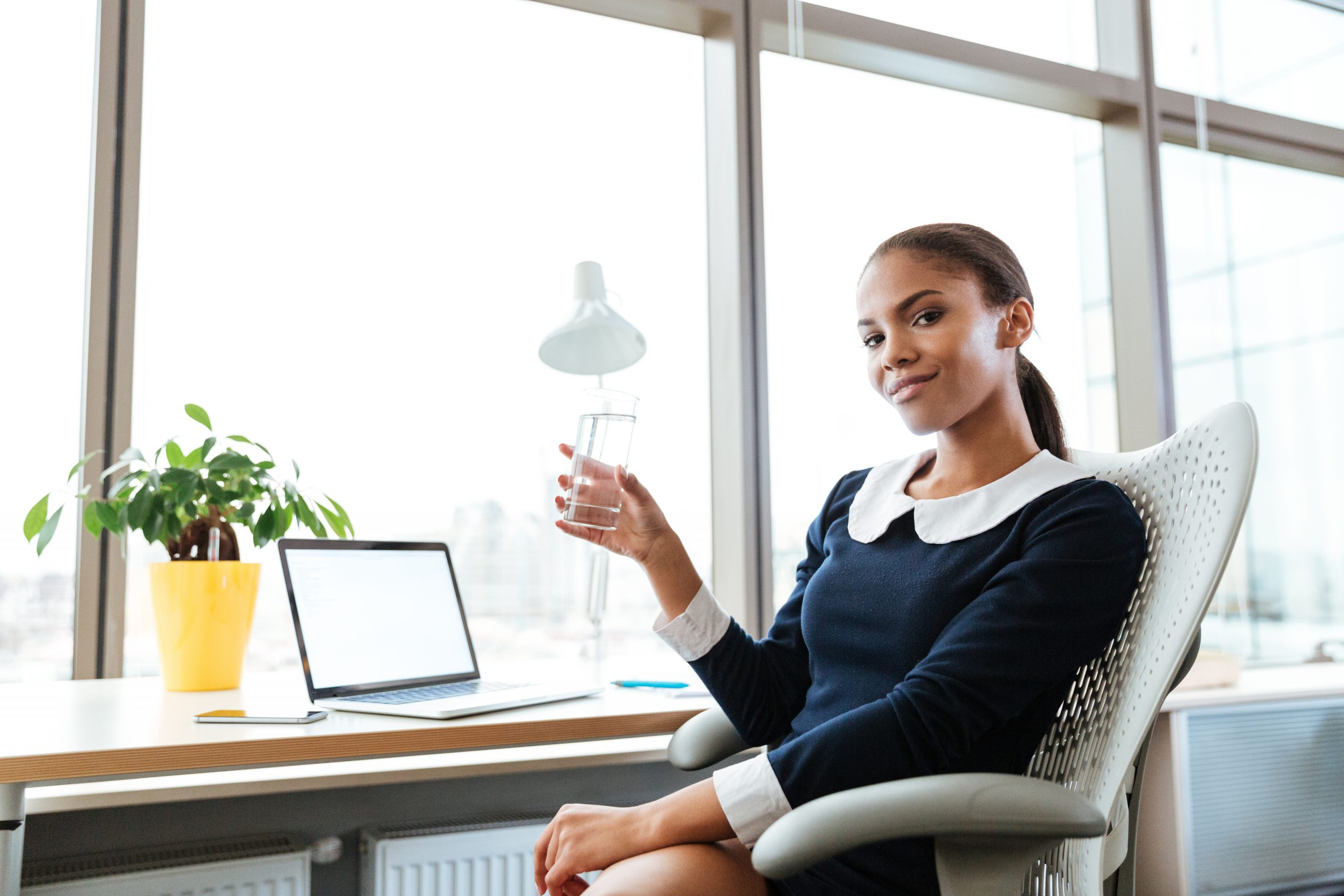 graphicstock smiling afro business woman in dress sitting by the table near the window with cup of water in hand and looking at camera in office HIhk8Pm ne scaled