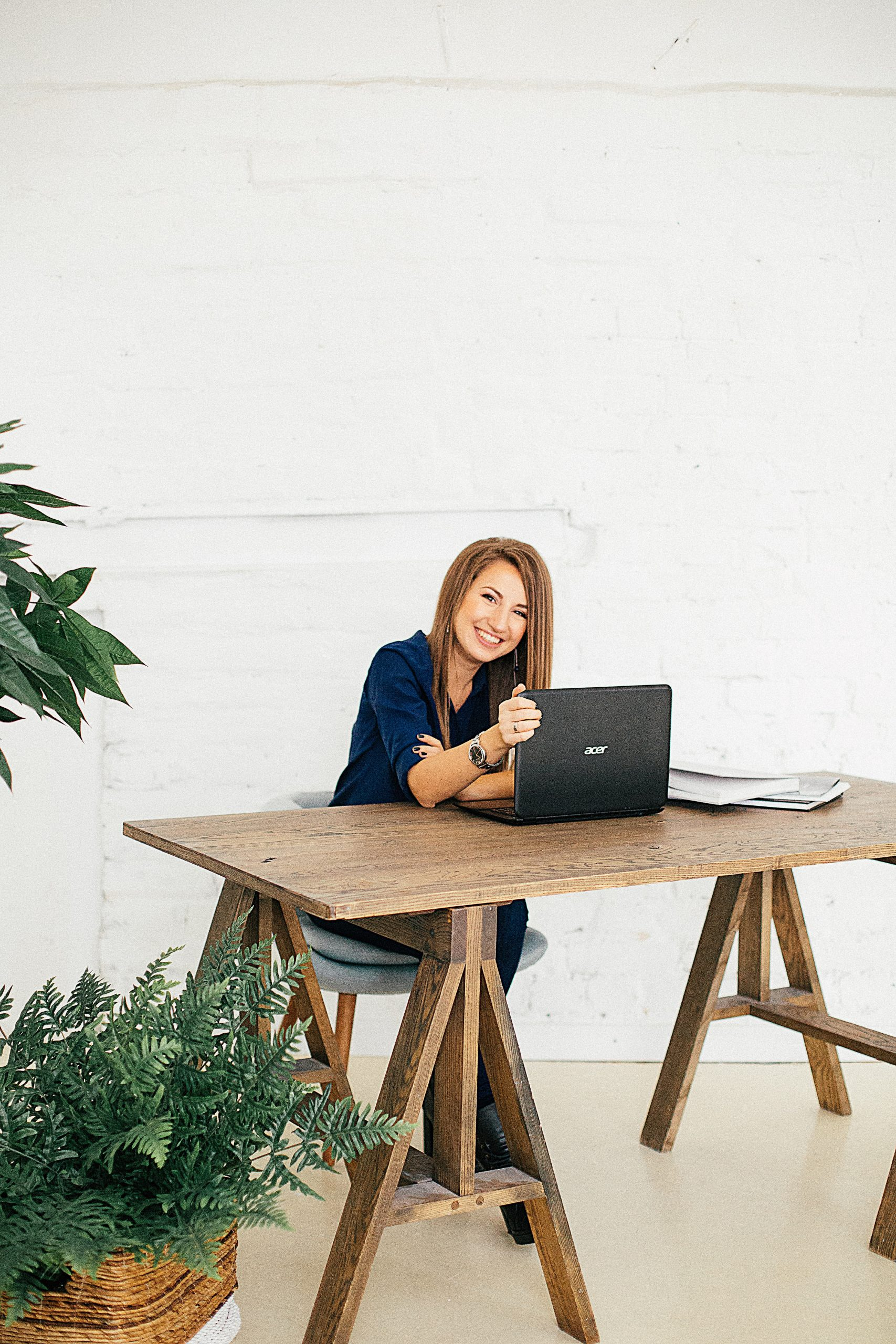 woman in wooden table using computer behind white wall 3681589 scaled